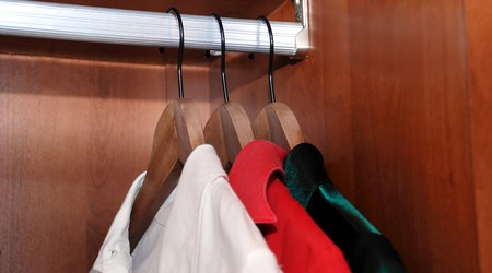 three clothes-hanger with chemises in wooden wardrobe photo