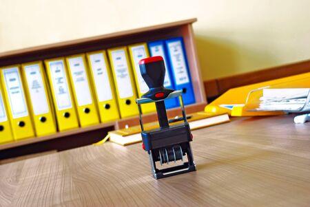 attest: Black stamp on wooden desk in office over files background