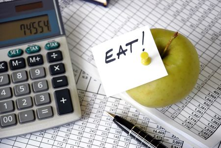 foresee: eat reminder on apple among papers and calculator Stock Photo