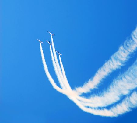 pirouette: planes group in acrobatic flight with smoke trace over blue sky Stock Photo