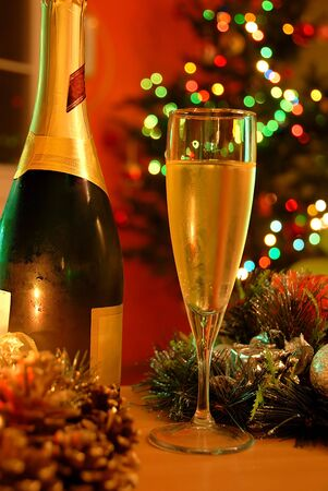 glass of champagne and bottle over new year tree photo