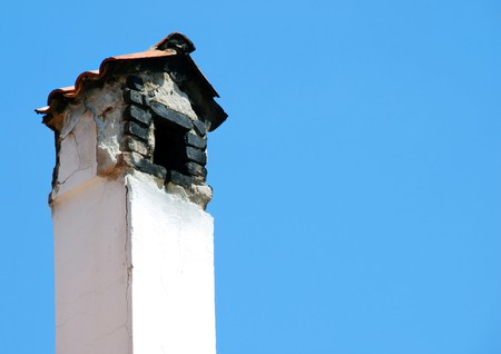 Old smoky chimney isolated over blue sky Stock Photo - 4211647