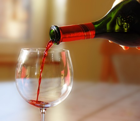 Pouring red wine into wineglass from green bottle photo