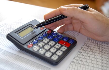 man hand holding pen on calculator buttons in office Stock Photo - 4421303