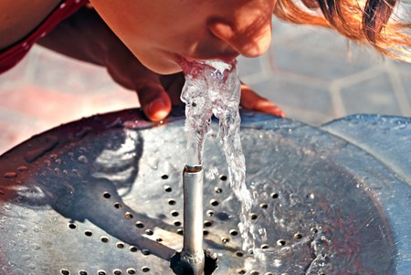 Girl drinking on water fountain outdoor close up photo