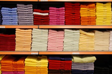 new colorful towels stacks on shelves in store Stock Photo