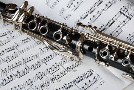black clarinet over opened music sheet photo