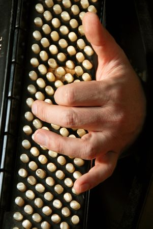 musician hand playing accordion closeup in dramatic shadows photo