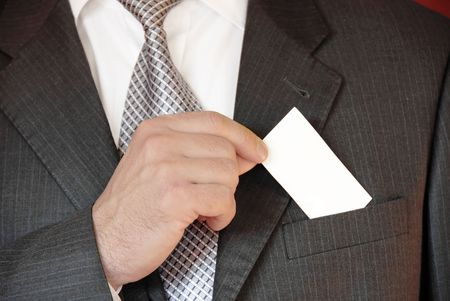 businessman hand holding a business card over suit pocket