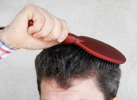 hand on forehead: Mature man brushing black greyish hair with red hairbrush Stock Photo