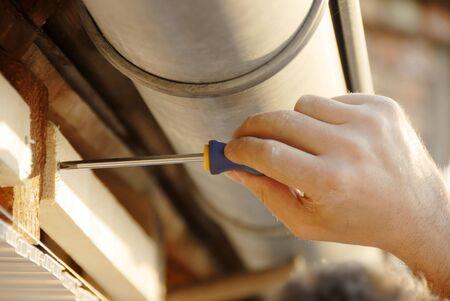 toiture maison: Travailler main en plissant sous le toit de la maison en plein air