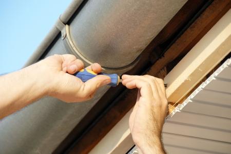 toiture maison: travail des mains de vissage sous toit maison de plein air