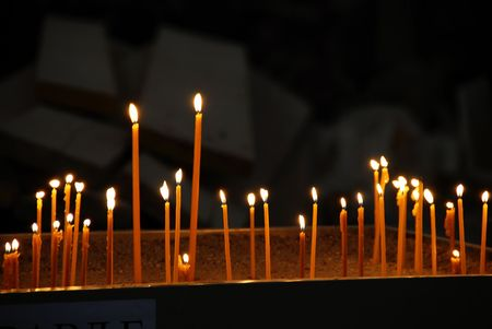 yellow candles burning in orthodox church over dark background photo