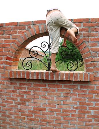 barefooted child climbing on brick fence from back Stock Photo