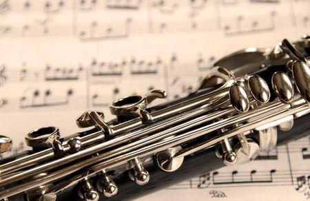Fragment of black shining clarinet over opened music book photo