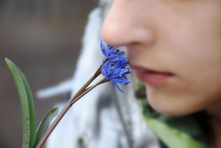 smells: blur girl smells blue spring flowers closeup