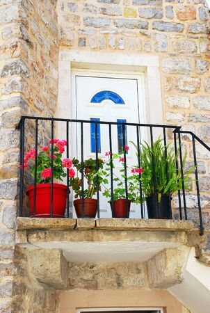 Entrance door of old stone house with flowerpots in Budva photo