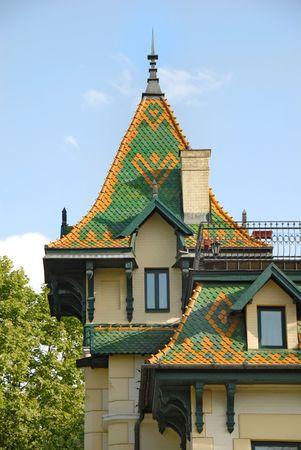 chimney corner: techo verde de alta en la construcci�n de amarillo sobre el cielo azul