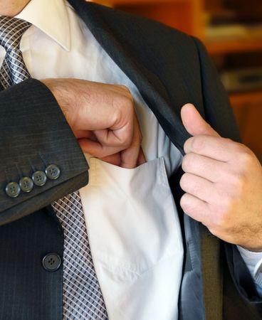 put: Businessman hand  in inner jacket pocket