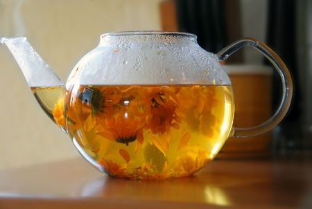 tea from calendula flowers in glass transparent teapot Stock Photo