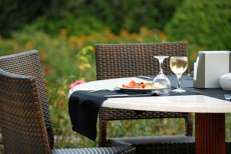 patio chair: outdoor table with served plate and wine glasses Stock Photo