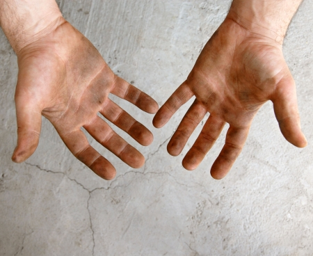 the left: male dirty hands over gray concrete background