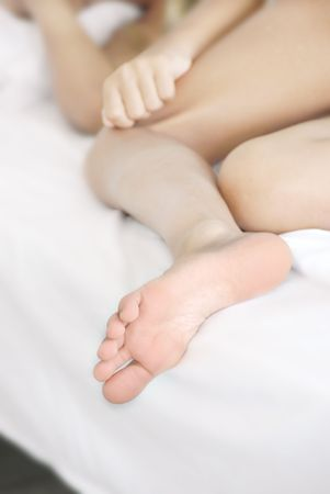 young sleeping girl foot closeup on bed photo