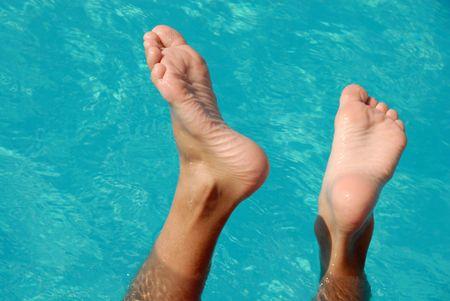 pies descalzos: chico h�medo pies sobre el agua de la piscina transparente azul  Foto de archivo