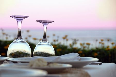 outdoor table with wine glasses over magenta sky Stock Photo