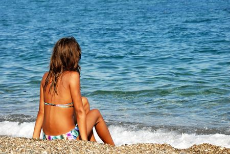young girl long brown hair sitting on beach photo