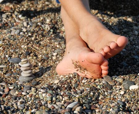 feet crossed: child feet next to rocks stack on beach