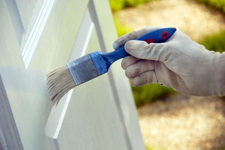 painting wooden door in white color by blue brush photo