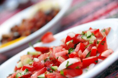 cut tomato pieces with parsley on plate closeup photo