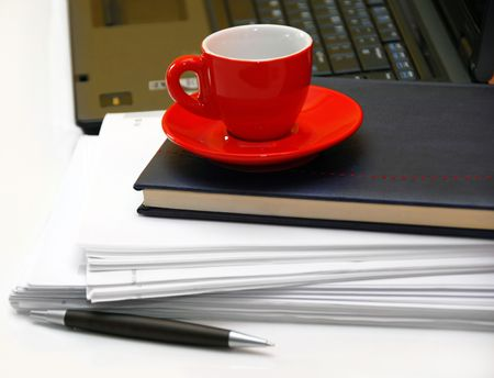 writing utensil: red coffee cup over black notebook on office desk Stock Photo