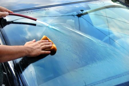 hands with hose and sponge washing blue car glass photo