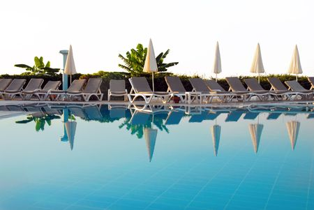 chairs row by blue swimming pool in resort in Turkey photo