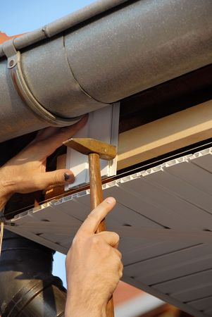 assiduous: working hand with hammer and nail under house roof outdoor Stock Photo