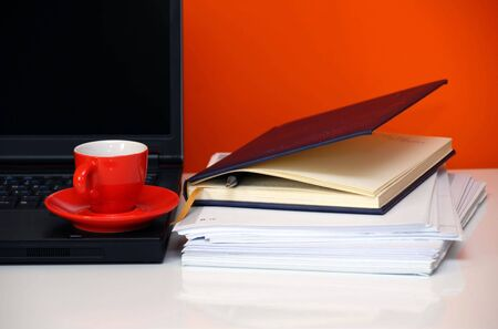 writing utensil: red cup over black notebook on office desk still life