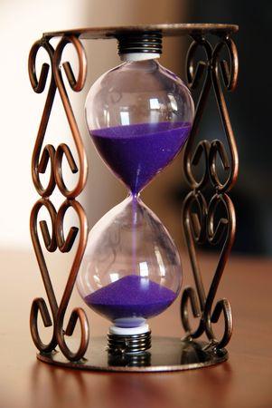sand clock on desk closeup, time passing concept photo