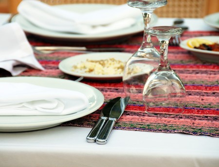 served table with plates, silverware and turned wineglasses Stock Photo - 6967125