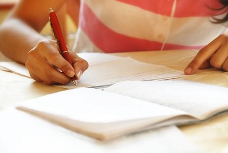 schoolgirl with pen writing down in notebook homework Stock Photo