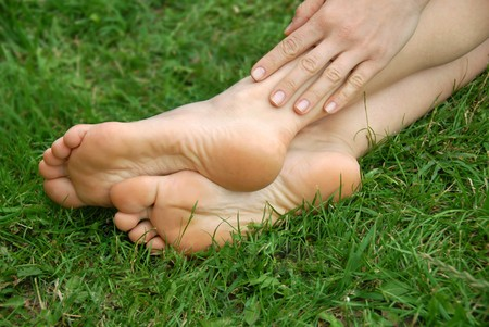 woman healthy feet and hand over green grass outdoor