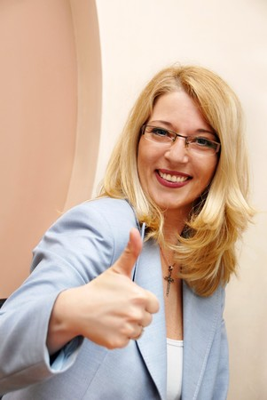 blond smiling businesswoman in glasses showing ok sign Stock Photo - 7158451