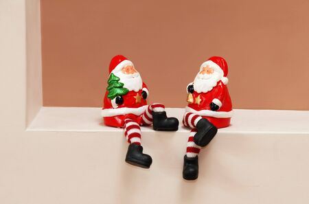 clauses: two red porcelain Santa Clauses toys sitting