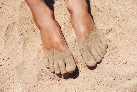 piedi del ragazzo in giallo sabbia sulla spiaggia closeup
