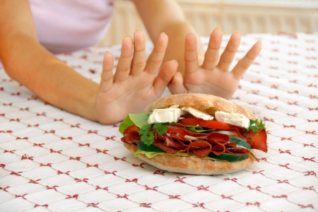 refusing: female hands refusing big meat sandwich with ham and cheese