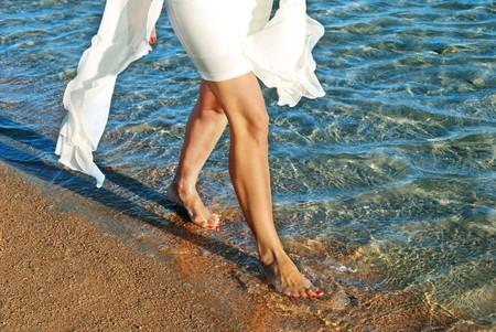 legs of woman in white dress walking on beach by blue sea water photo
