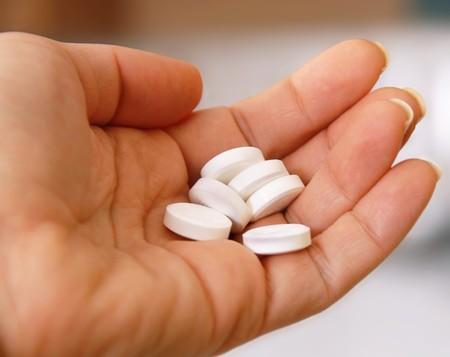 pharm: several white round pills on hand closeup