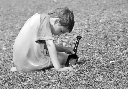 little boy sitting on pebble playing with plastic shovel in black and white photo
