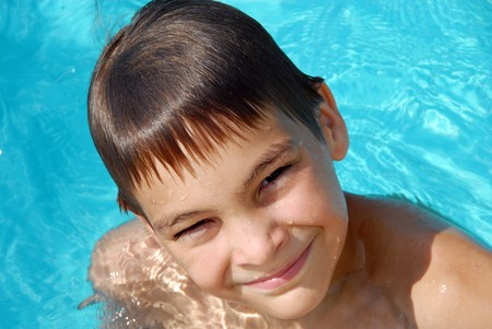 happy teen boy in blue swimming pool portrait photo